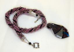 Magnifique collier de perles de verrede couleur vieux rose avec insertion de perles noires son pendentif qui est dans le centre du collier est vieux rose avec du noir et du gris. Son fermoir décoratif est facile à manipuler. Les frais de livraison sont gratuits pour le canada, cependant nous livrons dans le monde entier le prix de ce collier qui est une création unique est de 69.99 $