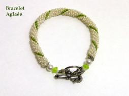 Bracelet de perles blanches avec insertion de perles vertes attache pour les personnes qui ont de la difficulté. Il y a aussi une chaine de sécurité