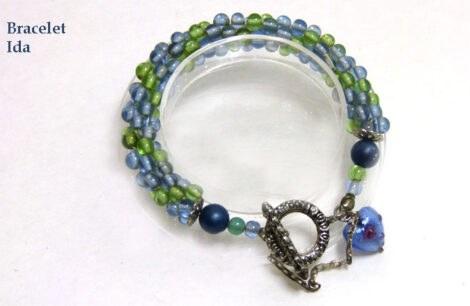 Bracelet de perles de verre bleues avec insertion de perles vert fermoir facile pour attacher le bracelet avec une chaine de sécurité et un petit coeur bleu en verre.