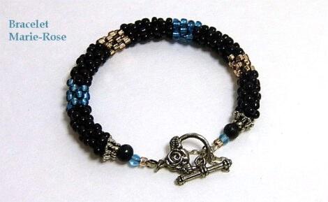 Bracelet de perles Marie Rose Ce bracelet est crocheté avec des perles noires avec insertion de perles beige et turquoise. Je crochète un tube par l'intérieur avec les perles à l'extérieur. Il est fait de perles noires avec insertions de perles turquoise et beige. Son fermoir est idéal pour les personnes qui ont de la difficulté avec les mains. Il y a aussi une chaine de sécurité. La livraison est gratuite au Canada