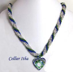 Collier de perles de verre, composé de verre transparent, aussi de couleur bleue et vert. La pièce de verre central est un magnifique coeur dans les mêmes couleurs.