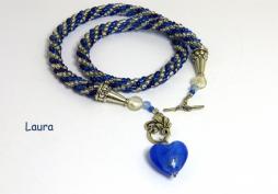 Collier de perles de rocaille fait au crochet de couleur bleue avec insertion de perles verre transparent, Il est terminé avec un fermoir décoratif et facile pour attacher le collier. Joint a ce fermoir il y a un petit coeur bleu qui termine avec élégance ce dernier